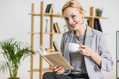 portrait of smiling businesswoman with book and cup of coffee in office