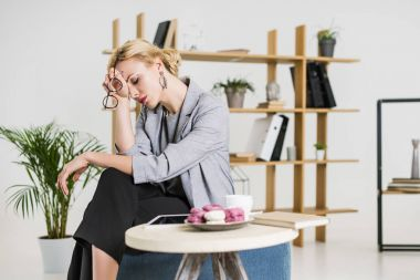 portrait of tired businesswoman sitting at coffee table in office
