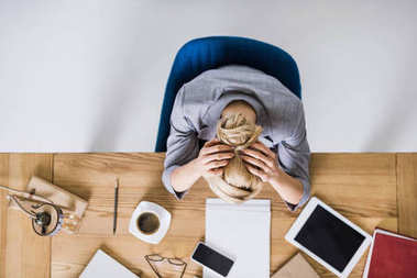 overhead view of tired businesswoman leaning on workplace in office