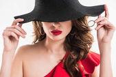 vonzó divatos lány bujkál a szemem alatt elszigetelt fehér fekete kalap