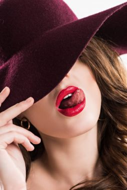 sexy woman sticking tongue out and hiding eyes under burgundy hat