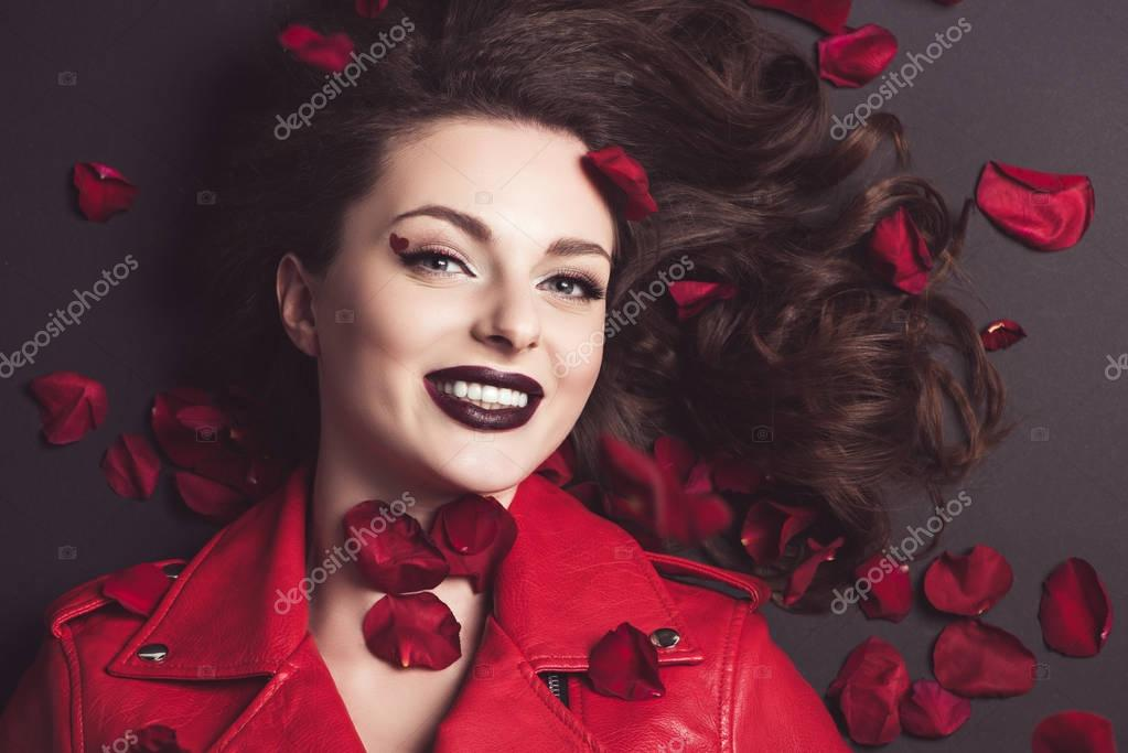 top view of smiling girl lying with roses petals, valentines day concept
