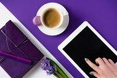 oříznutý obraz ženy pomocí tabletu stolu bílé a fialové