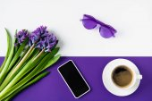 Fotografie top view of bouquet of purple hyacinth flowers and smartphone on table