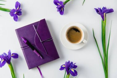top view of cup of coffee and scattered iris flowers on white table