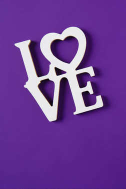 top view of word love isolated on purple, valentines day concept