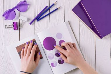 cropped shot of woman pointing at design book at workplace