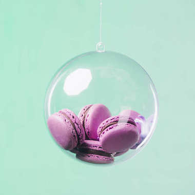 macarons in glass ball hanging on turquoise background