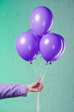 Cropped shot of woman holding purple helium balloons stock vector