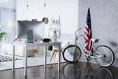 Photo silver computer on table and bicycle near wall in room