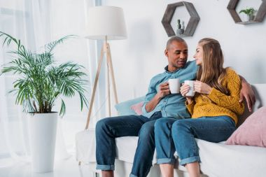multicultural couple sitting on sofa with coffee