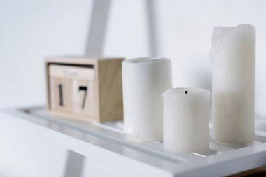 three white candles on white shelf