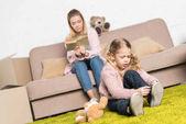 dítě nosit boty na koberci při čtení knih na pohovce matka