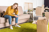 usměvavá mladá žena sedící na gauči při balení kartónové krabice během přemístění