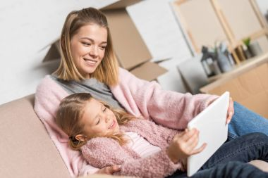 happy mother and daughter using digital tablet during relocation