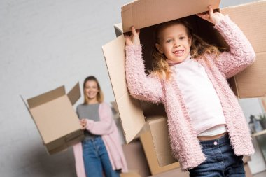 Happy mother and daughter holding cardboard boxes while moving home stock vector