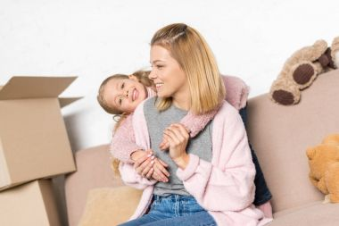Happy mother and daughter hugging while sitting on sofa during relocation stock vector