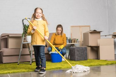 mother and daughter cleaning room with mop and bucket while moving home