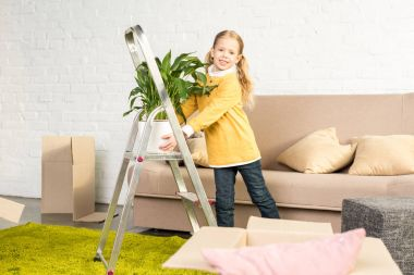 adorable little child holding houseplant and smiling at camera while moving home