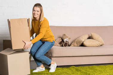 Woman holding cardboard box and smiling at camera while relocating stock vector
