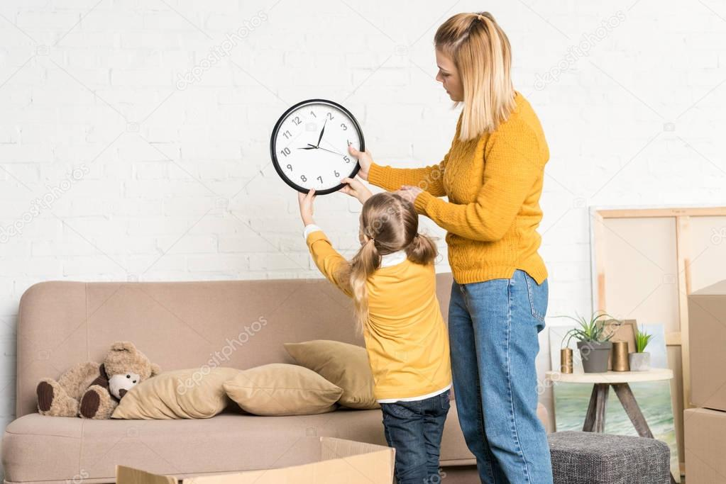 beautiful mother and daughter hanging clock on wall during relocation