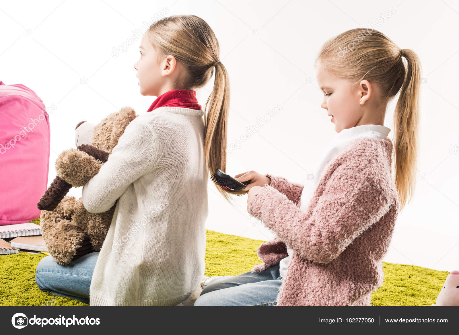 happy child brushing hair sister while sitting floor