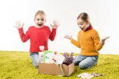 Fotografie excited little sisters with box of materials for art sitting on floor isolated on white