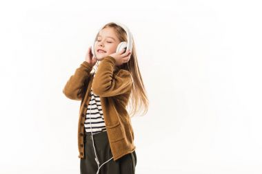 joyful little child listening music with headphones isolated on white