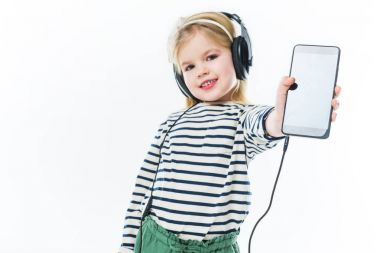 happy little child listening music with headphones and showing smartphone isolated on white