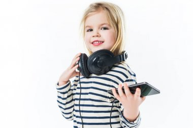 beautiful little child with headphones and smartphone isolated on white