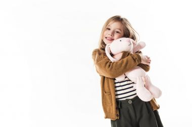 happy little child embracing with soft toy bunny isolated on white