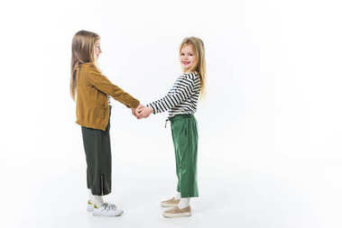 adorable little sisters holding hands isolated on white