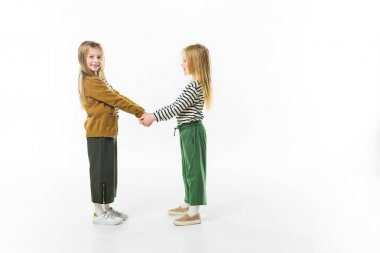 little sisters in stylish clothing holding hands isolated on white