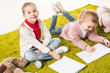 beautiful little sisters drawing together on floor isolated on white