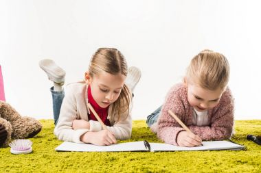 focused little sisters drawing with color pencils together on floor isolated on white