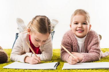 happy little sisters drawing with color pencils together on floor isolated on white