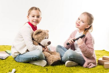 little sisters spending time together while sitting on floor isolated on white