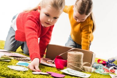 close-up shot of little sisters making diy greeting cards isolated on white