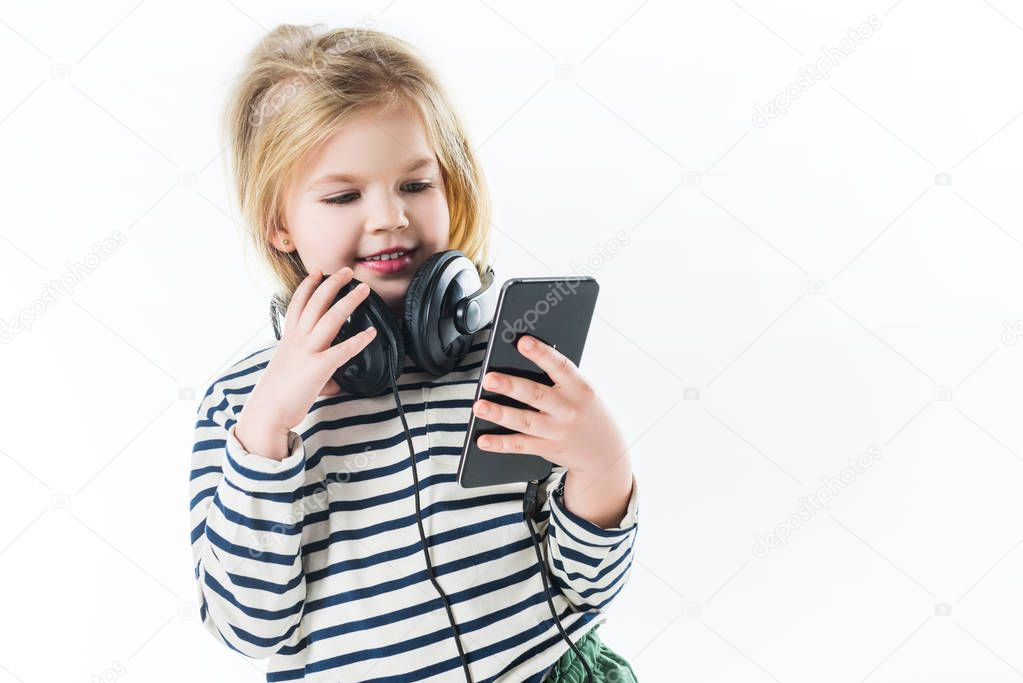 smiling little child with headphones and smartphone isolated on white