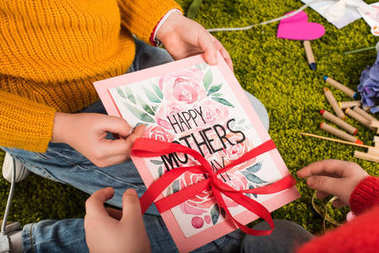 cropped shot of little children preparing greeting card for mothers day