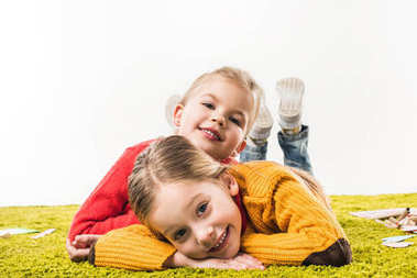 happy little sisters isolated lying on green carpet and looking at camera isolated on white