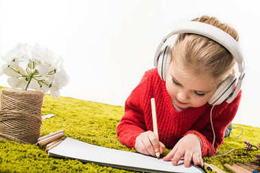 focused little child drawing with color pencils and listening music on green soft carpet isolated on white