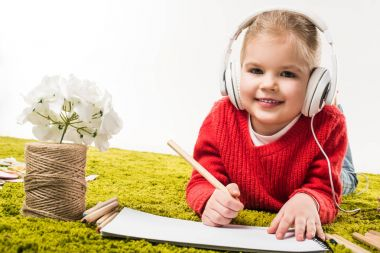 Happy little child drawing with color pencils and listening music on green soft carpet isolated on white stock vector