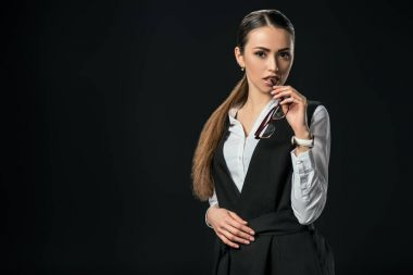 young beautiful businesswoman holding eyeglasses, isolated on black