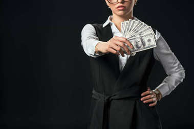 cropped view of businesswoman holding dollar banknotes, isolated on black