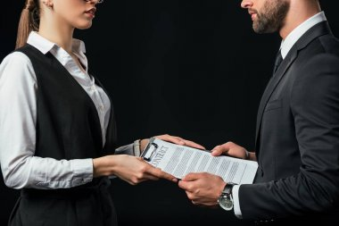 business colleagues holding contract, isolated on black