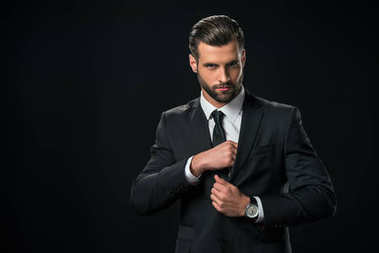 handsome businessman taking something from pocket of jacket, isolated on black