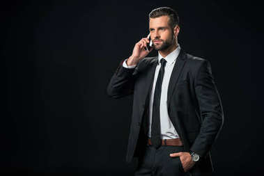 handsome businessman in jacket talking on smartphone, isolated on black