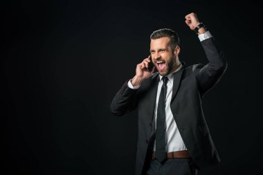 excited businessman in jacket celebrating while talking on smartphone, isolated on black