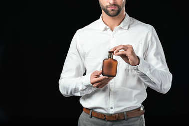 cropped view of businessman in white shirt holding perfumes, isolated on black